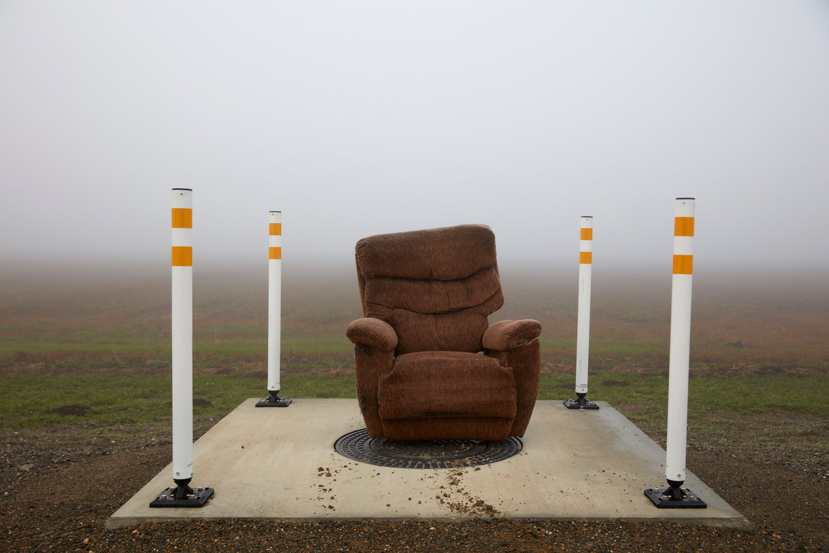 Brown Lounge Chair on Concrete Pad in the Fog