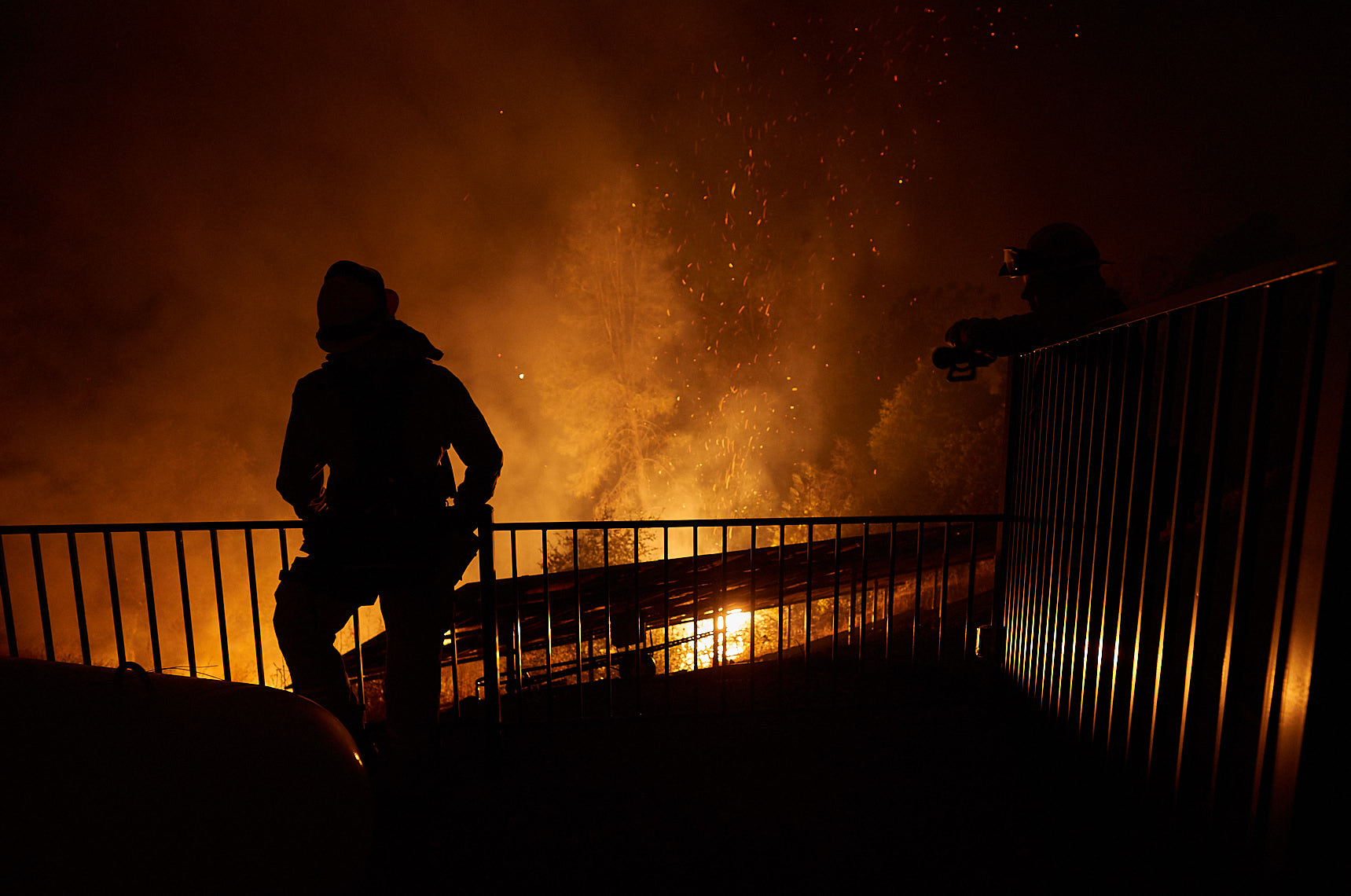 Silhouetted firefighter watches advancing flames