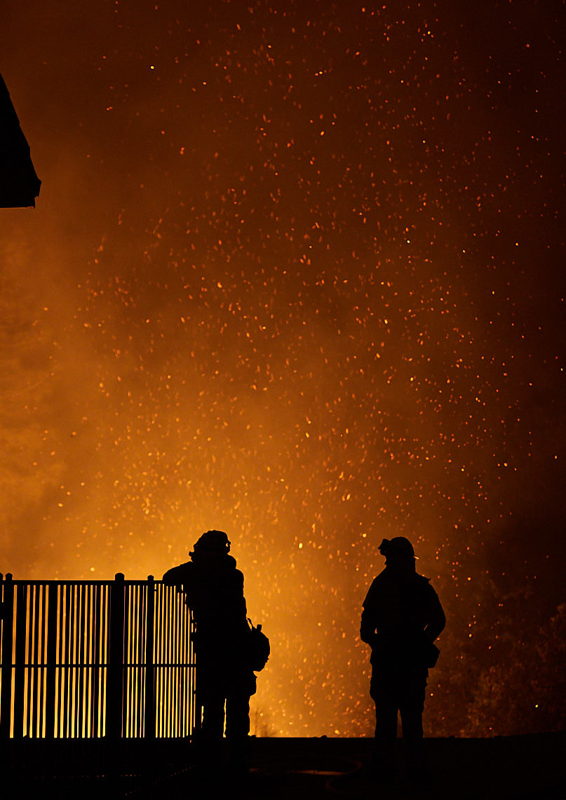 Silhouetted firefighters watch advancing flames