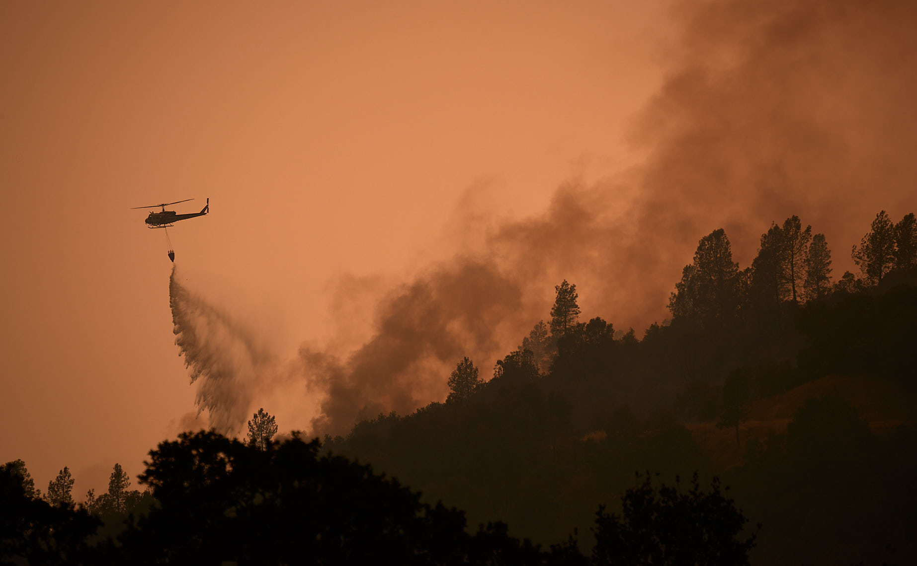 Silhouetted Helicopter Drops Water on Wildfire