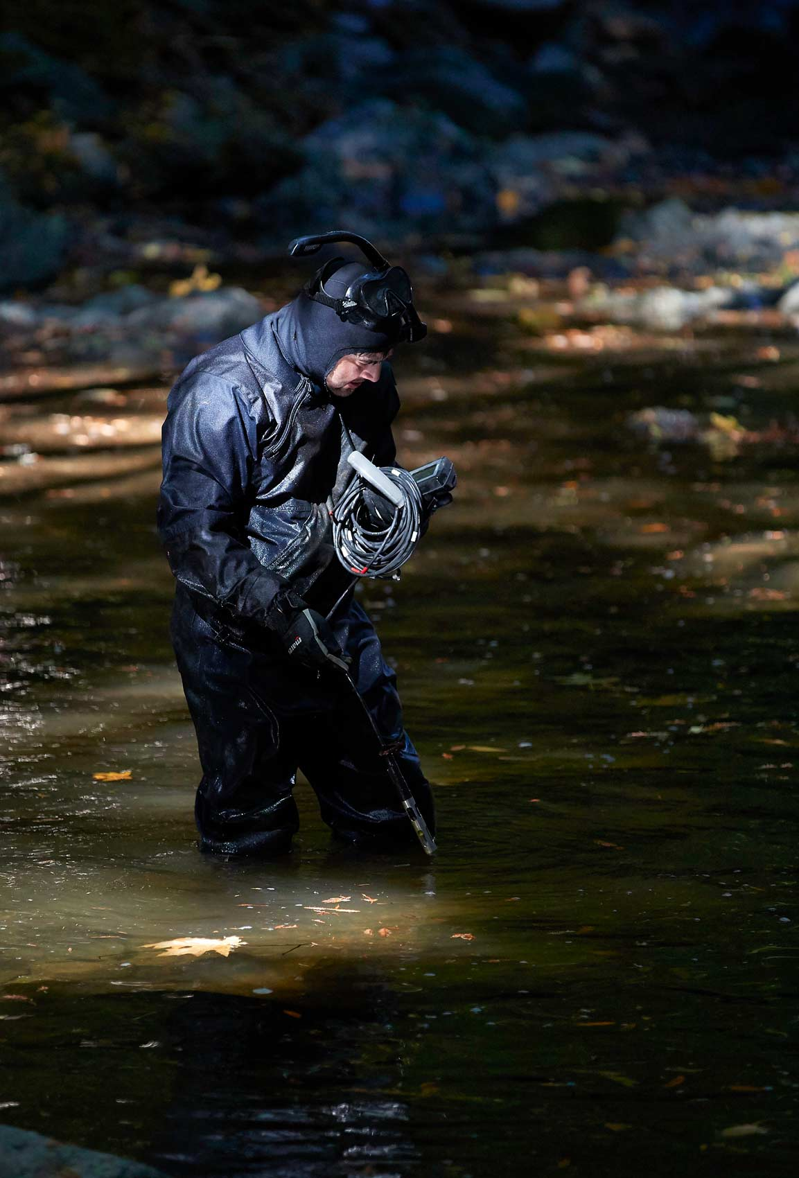 Researcher in Wetsuit Takes Oxygen Measurement in Stream
