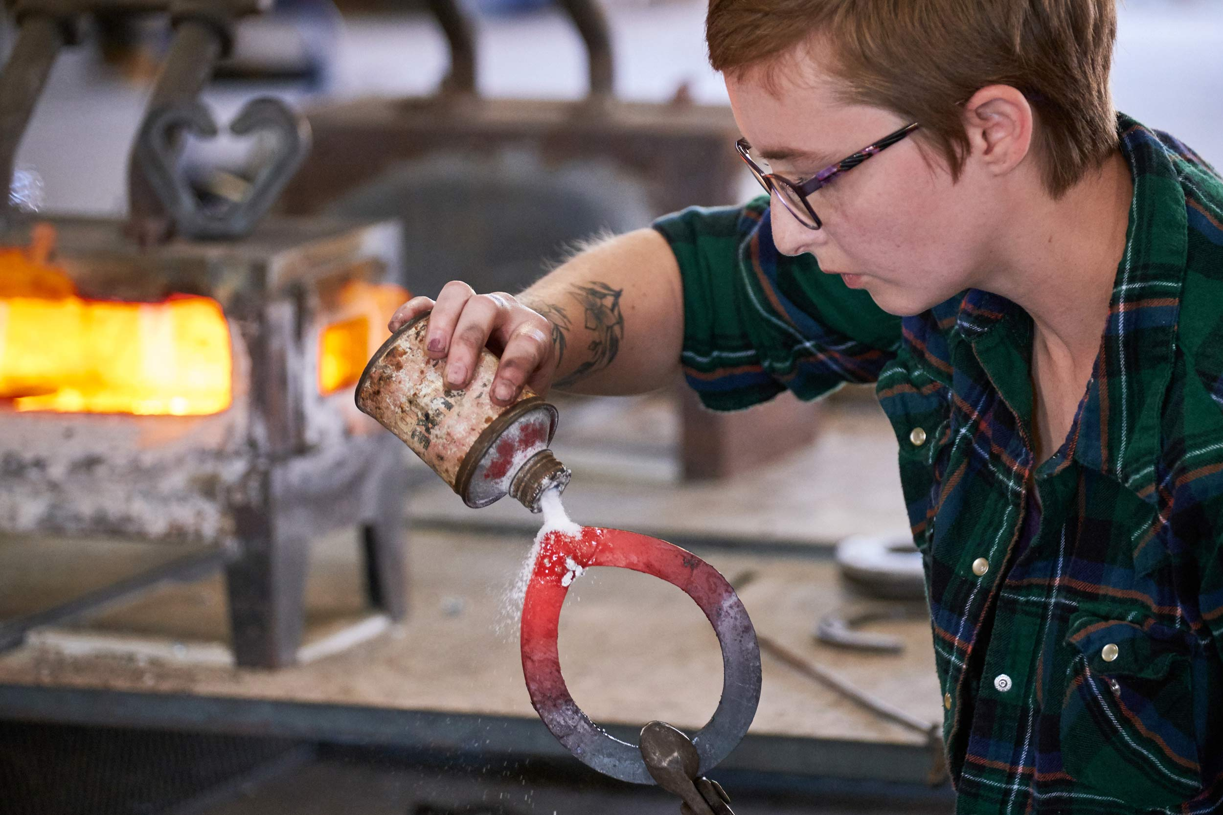Student Powders a Horseshoe after Removing it from Forge