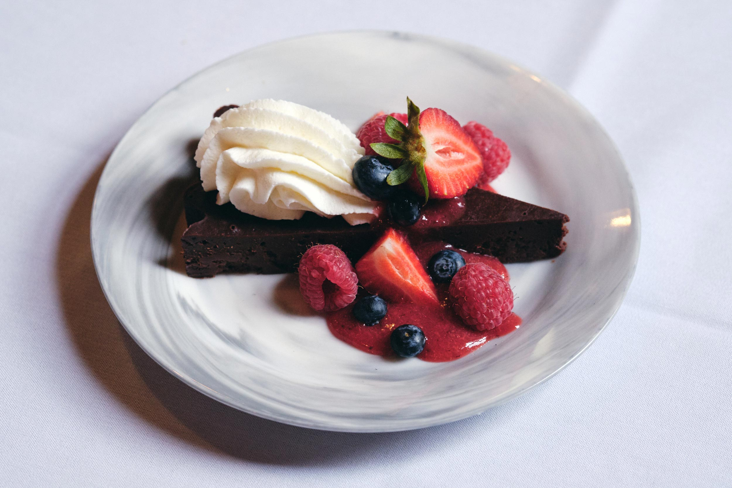 Rich Chocolate Cake with Berries and Whipped Cream