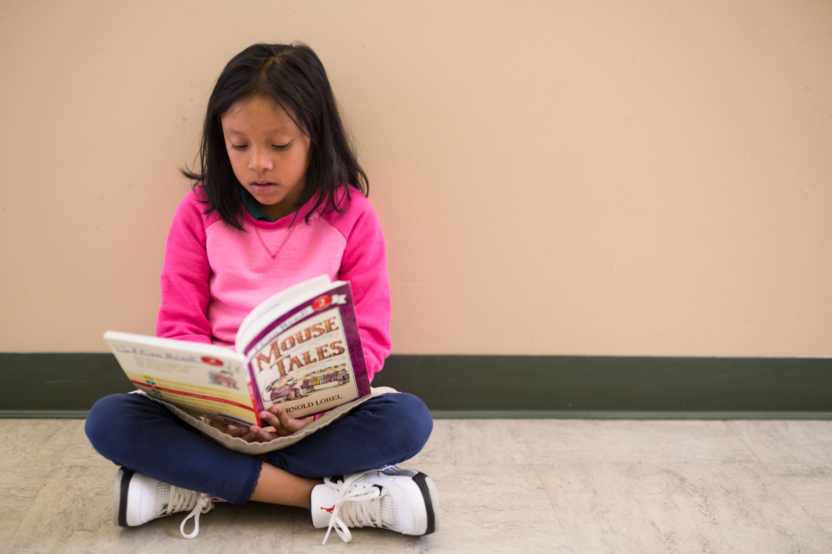 Girl Reads in Hallway at School