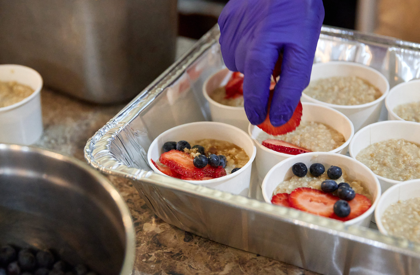 gloved_hand_puts_berries_on_oatmeal_3FG7961